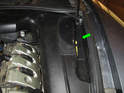 Open the hood and remove the access panel on the right side of the engine with the battery symbol on it (green arrow).