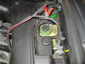 Connect the battery charger or jumper cables to the connection points starting with the positive terminal first (green arrow) and then the negative.