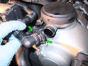 Squeeze the tabs (green arrows) on the breather hose leading to the air-oil separator and pull it off.