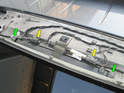The third brake light assembly is held in place by two T20 Torx screws (green arrows).