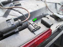 Now push the tab (green arrow) and pull the electrical connector off the brake light assembly.