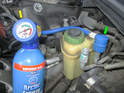 If you are using a gun-style can of refrigerant as shown here, connect the hose to the low side pressure port (green arrow).