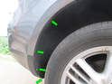 Left and Right Sides: Loosen and remove the four T25 Torx screws holding the wheel liner to the edge of the bumper cover (green arrows).