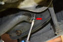Use a flathead screwdriver and remove the hose clamp and hose from the oil tank (red arrow).