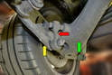 This photo illustrates how the drop link (red arrow) attaches the banana arm (green arrow) to the sway bar (yellow arrow).