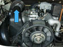 The heater blower motor is located on the upper left side of the engine, below the rear hood hinge (blue arrow).