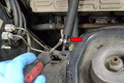 Use a flathead screwdriver and carefully disconnect the rubber return line from the metal line (red arrow).