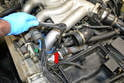 Using your 13/16-inch spark plug socket and an extension to clear the intake runner, remove the plug from the engine (red arrow).