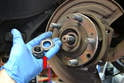 With the nut lose you can remove both the nut and the large washer from the axle (red arrow).