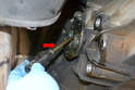 Remove the long axle flange bolt (red arrow).