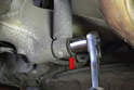 Begin by using a 22mm socket or wrench to loosen the lower shock bolt (red arrow).