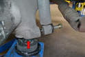 With the bolt loosened, support the trailing arm with a jack (red arrow) to take the weight off the bolt.