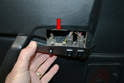 With the lower screws removed you can pull the switch plate out from the metal retaining clip on the upper section of the door panel (red arrow).