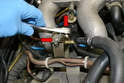 Remove the two 10mm bolts holding the regulator to the fuel rail (red arrows).