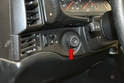 The headlight switch is just to the left of the steering column.