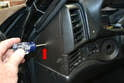 Using a Philips head screwdriver remove the single screw on the end of the dash trim piece (red arrow).