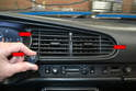 Use a longer handled Philips head screwdriver and remove the three screws that you access through the vents (red arrows).