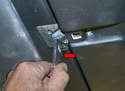 Release the two clamps on the inside front of the sunroof by folding them forward (red arrow) with your hand.