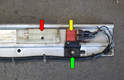 The early sunroof assembly has a guide rail attached to the sunroof motor, which extends toward the rear of the car.
