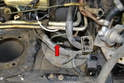 Use a 12mm flared nut wrench and disconnect the hydraulic line from the master cylinder (red arrow).