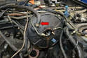 Move to the engine area and disconnect the check valve hose from the booster (red arrow).