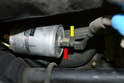 Brace the fitting on the filter (red arrow) with a 19mm wrench and use a 18mm wrench to remove the line (yellow arrow).