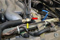 Support the 24mm nut on the dampener (red arrow) and use a 19mm wrench to loosen the fuel supply line (yellow arrow).