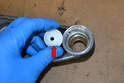 You can use the plastic lower bushing (red arrow) to firmly press the upper bushing into place in the control arm.
