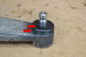 Push the boot over the top of the ball joint until the spring clips on the top and bottom of the boot slip into their grooves (red arrows).