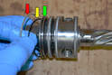 On the pinion there are four grooves; remove the Teflon O-ring (red arrow) and then the rubber O-ring (yellow arrow) from each groove (green arrow).