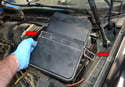 Next, release the two clips on the fuse/relay panel cover (red arrows) and remove it from the vehicle.