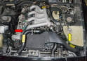 Move to the top of the engine and open the cap on the coolant reservoir to help break the vacuum seal and drain the fluid (yellow arrow).