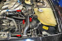 You will need to remove the manifold air intake tube to get access to the coolant hoses and cross over pipe on the left side of the motor.