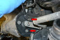With the arm moved, remove the two 10mm side bolts (red arrows).