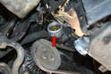 With the hose removed you can see the thermostat in the coolant pump housing (red arrow).