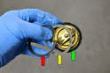 This photo illustrates the thermostat with the snap ring (red arrow), the spacer (yellow arrow) and the O-ring (green arrow).