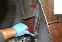 Remove the three 10mm bolts holding the cover to the fenders on both sides (red arrows).