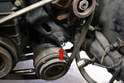 To replace the alternator and A/C belt, begin by using a 17mm wrench and loosening the pivot bolt on the A/C compressor (red arrow).