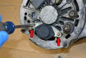 With the alternator on your bench you will want to remove the two Philips heads screws holding the regulator in place (red arrows).