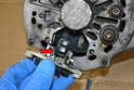 Pull the regulator (red arrow) out from the alternator.