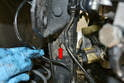 On the underside of the frame rail is a connection that holds the wiring for the brake sensor and the power steering cooling line (red arrow).