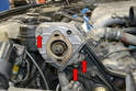 Remove the three 10mm bolts holding the distributor cover plate in place (red arrows).