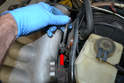 Use a 10mm wrench and remove the single bolt holding the oil dipstick tube to the manifold (red arrow).