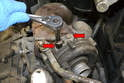 Use a 13mm socket and remove the two bolts (red arrows) holding the oil line to the top of the turbo.