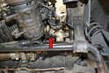 The second mounting bolt is located under the engine support above the steering knuckle (red arrow).