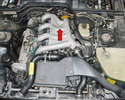 The air oil separator (AOS) is located on the left rear of the engine under, well just about everything (red arrow).