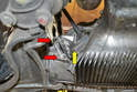 Working on the left side, use a 10mm wrench and remove the two bolts (red arrow) holding the shield in place (yellow arrow).