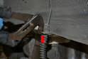 Remove the mounting clip that holds the lines to the body bracket by pulling it out with a set of pliers.