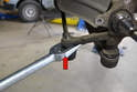 Depending on the age and condition of the tie rod end, you may need to use a pickle fork or ball joint remover (red arrow) to separate the ball joint from the spindle.