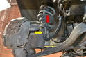 Remove the brake wear sensor (red arrow) and the hydraulic brake line (yellow arrow) from the mounting brackets on the strut.